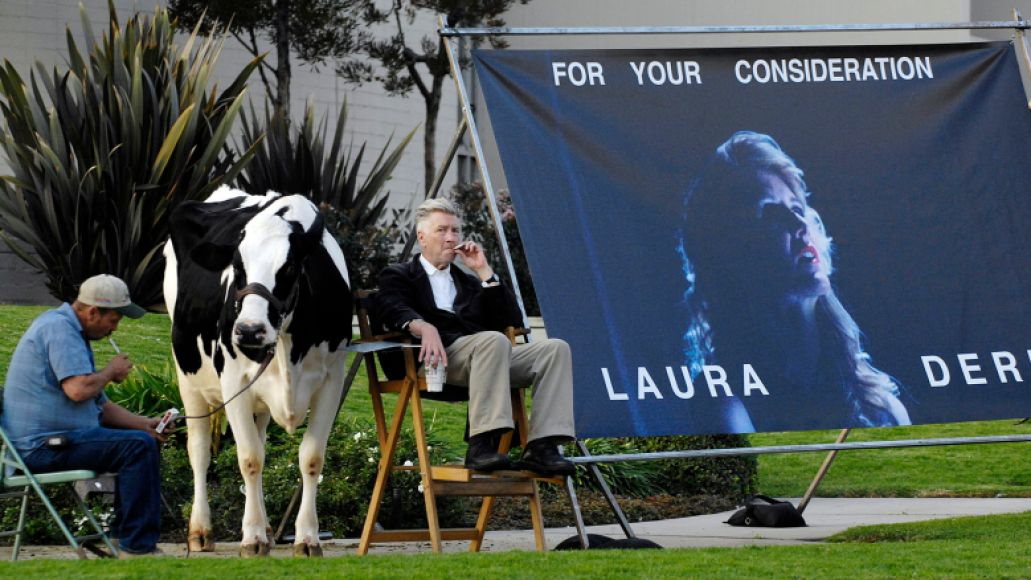 """""""Inland Empire"""" writer/director David Lynch (R) is joined by a live cow and its handler Mike Fanning as he promotes the film's star Laura Dern for movie awards season at the intersection of Hollywood Blvd. and La Brea Ave. in Los Angeles"""